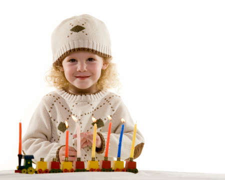 chanukkah: Young blond hair three year old boy lighting the candles in the Jewish tradition to celebrate Hanukkah