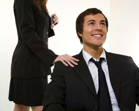 delegar: Hombre de negocios de sentarse con una expresi�n feliz so�ando y una mujer de pie detr�s de �l con la mano en el hombro