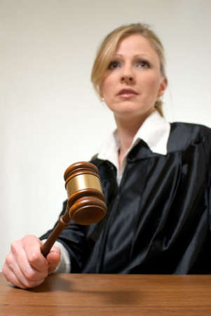 Blond woman judge holding a gavel with serious expression focus on the gavel photo