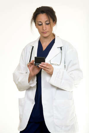 Hispanic Woman doctor in her 30s holding a pager and looking down reading a pager photo