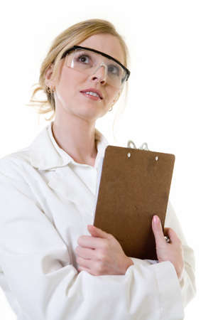 Attractive blond woman in white lab coat holding a chart or clipboard and safety goggles looking up standing on white photo