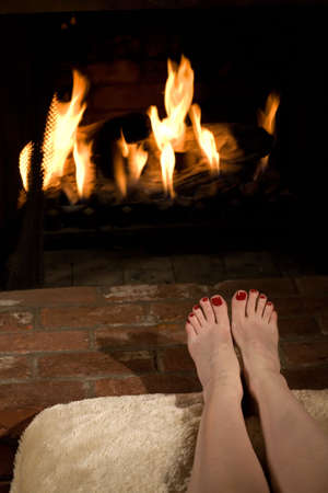 Woman's bare feet with red painted toe nails on a foot stool near a home fireplace Stock Photo - 2400080