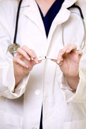 Body of a female doctor in lab coat focus on the hands holding a cigarette broken in half