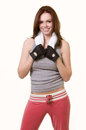 Attractive auburn haired woman in workout attire with towel around neck smiling standing on white