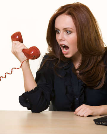 Young brunette woman in business suit sitting at a desk yelling into the receiver of a old style red rotary telephone photo