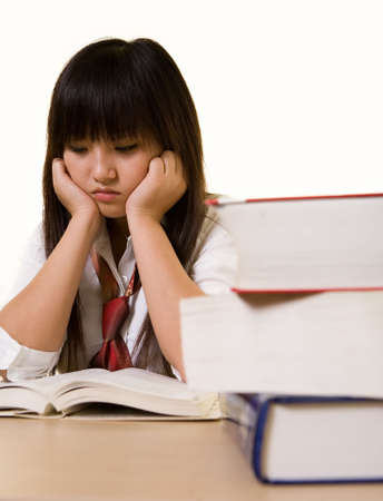 final thoughts: Young Chinese school girl wearing school uniform sitting in front of a pile of thick textbooks while reading one with a depressed expression on white Stock Photo