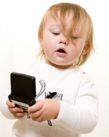 pager: Adorable caucasian blond  girl toddler sitting on the floor holding a text message pager