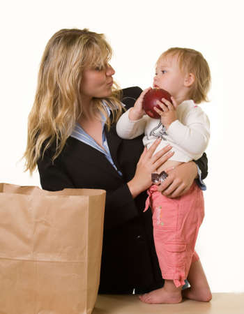 exasperated: Attractive blond woman in business attire carrying a young  girl while  is holding a large apple