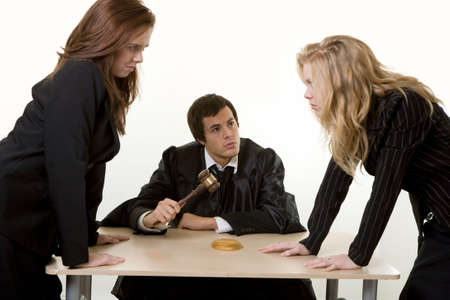 appearing: Male judge sitting at a desk with one female lawyer on each side appearing to be having a debate
