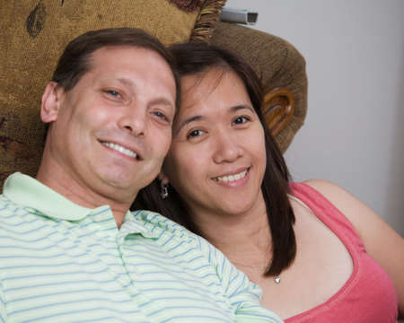 suitor: Portrait of a loving mixed race couple, Asian and caucasian smiling sitting in living room inside house