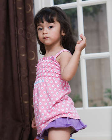 Cute little twee jarige brunette meisje draagt schattig roze zomer kleding binnenkant van herkomst