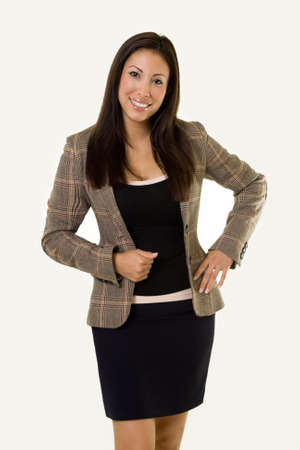 Attractive young Hispanic woman wearing a business suit jacket and skirt with hands on hips standing Stock Photo