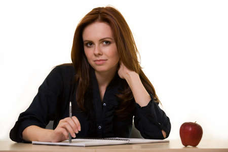 educating: Attractive auburn haired woman in dark colored business suit sitting at a desk with a nice friendly smile like a teacher