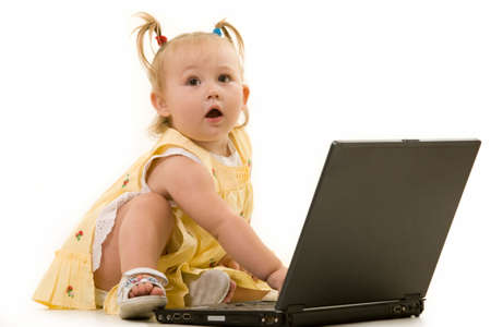 Adorable  girl toddler in pigtails sitting on the floor working on a laptop computer  Stock Photo - 2471576