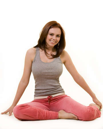 auburn hair: Attractive auburn hair or brunette woman in pink and grey workout attire  sitting on the floor over white background