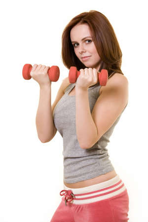 auburn hair: Attractive auburn hair or brunette woman in pink and grey workout attire holding 2 hand weights with serious expression over white Stock Photo