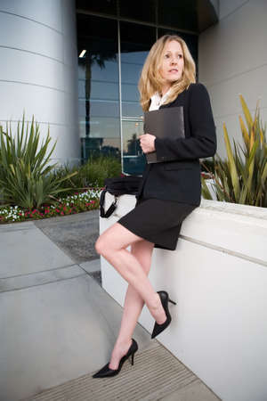 Attractive blond business woman wearing professional business suit standing outside a modern office building