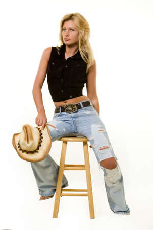 Beautiful blond woman wearing straw cowboy hat and a brown vest and faded ripped jeans sitting on a wooden stool over white  photo