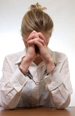 Blonde professional looking woman wearing a white collared shirt with hands cuffed hiding face in hands