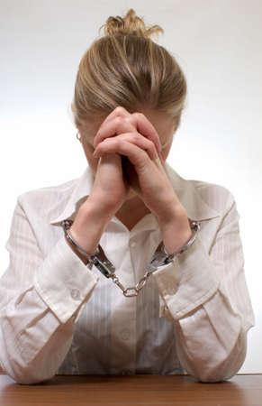 handcuffed: Blonde professioneel uitziende vrouw draagt een wit shirt met collared handen geboeid verbergen gezicht in de handen