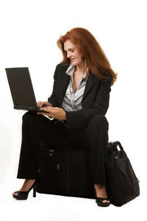 Full body of an attractive red hair woman sitting on a suitcase and typing on a laptop on white  photo