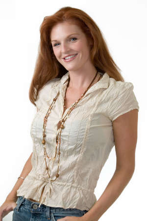 Attractive red hair woman wearing casual clothing and costume jewelry standing on white photo
