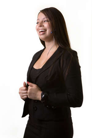 earpiece: Confident brunette Hispanic woman in professional business suit standing wearing a telephone earpiece with laughing face expression