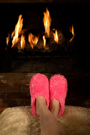 Legs of a woman with feet near a fireplace wearing warm big pink fuzzy slippers