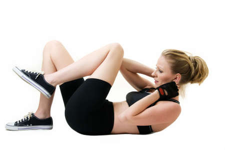 Attractive blond woman laying on floor wearing workout attire doing stomach crunches or sit ups over white