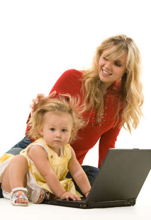 Adorable baby girl toddler sitting on the floor with mom working on a laptop computer  Stock Photo - 2590100