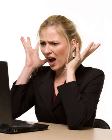 molesto: Atractiva rubia mujer llevaba traje de negocios sentado delante de un ordenador con la expresi�n facial enojado con las manos arriba mientras busca en el ordenador como si se rompi� o se estrell�