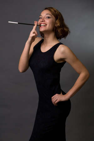 Young pretty brunette woman wearing a navy blue dress with a cigarette in a cigarette holder in her mouth posing sideways in profile photo