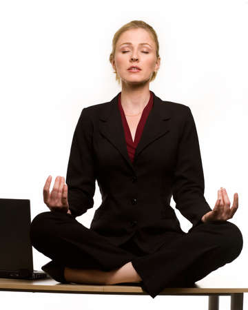 Attractive blond hair woman wearing business suit sitting crossed legged in the yoga lotus position on desk
