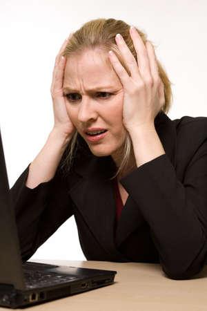 confused person: Atractiva rubia mujer llevaba traje de negocios sentado delante de un ordenador con enojado o confundido la expresi�n facial en la cara con las manos al tiempo que busca en el ordenador como si se rompi� o se estrell�  Foto de archivo