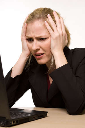 Attractive blond hair woman wearing business suit sitting in front of a computer with angry or confused facial expression with hands on face while looking at the computer as if it crashed or broke photo