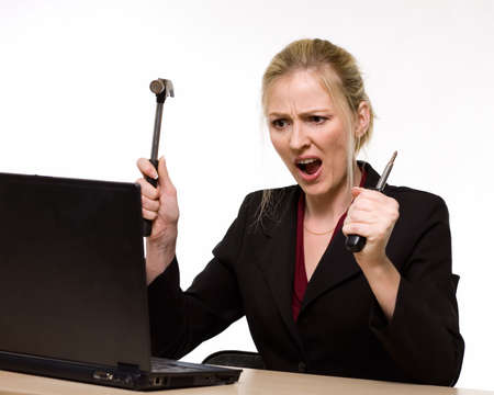 Attractive blond hair woman wearing business suit sitting in front of a computer with angry facial expression holding a hammer in one hand and a screwdriver in the other photo