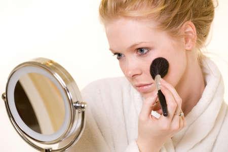mujer maquillandose: Atractiva mujer rubia aplicaci�n de maquillaje llevaba t�nica blanca con una ronda espejo de cosm�tica delante  Foto de archivo