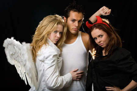 to tempt: An attractive young man standing in between a beautiful blond angel and a pretty brunette devil woman