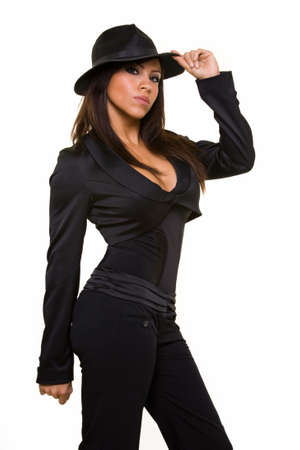 fedora: Attractive long hair brunette woman wearing sexy low cut black suit and black old gangster style fedora hat standing on white with serious expression