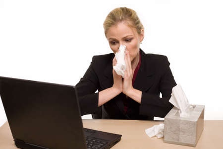 Attractive blond woman secretary sitting at office desk with a box of tissue on the desk while blowing her nose photo