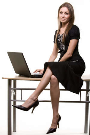 crossed legs: Full body of a young brunette business woman sitting on office desk beside laptop computer over light background Stock Photo