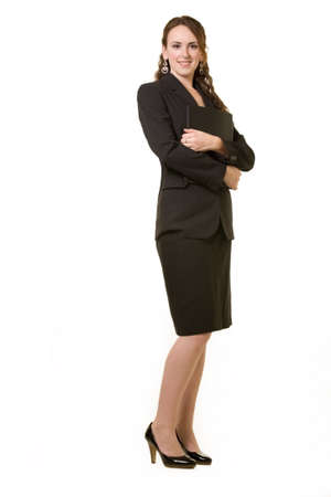 Full body of an attractive young brunette business woman wearing black business suit with arms crossed standing on white
