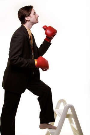 out of job: Young man in business suit wearing boxing gloves while climbing a ladder step stool concept fighting the business ladder to get to the top