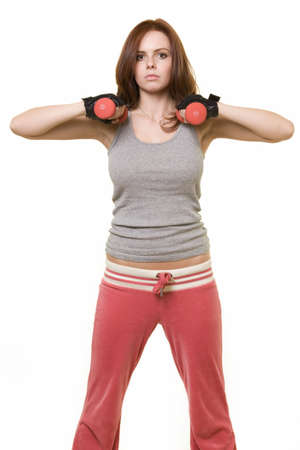 Attractive auburn hair or brunette woman in pink and grey workout attire holding 2 hand weights with serious expression over white Stock Photo