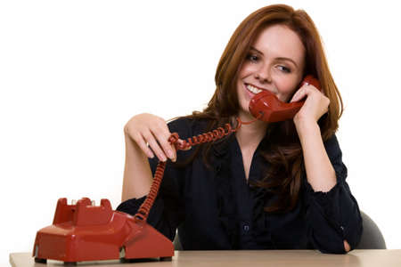 receiver: Attractive young brunette woman in business suit talking on an old style red phone smiling while sitting at a desk over white as if making personal phone calls while at work