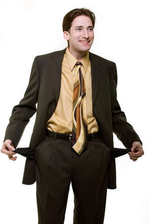 Young man wearing business suit holding on to empty pants pockets showing no money or broke photo