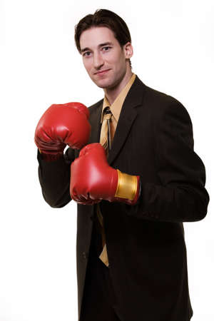 Young man wearing business suit standing on white wearing red boxing gloves Stock Photo