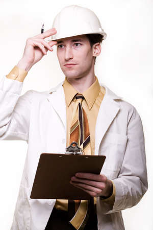coat and tie: Young attractive man wearing white lab coat tie and a white hard hat holding onto a clipboard