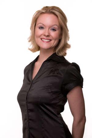 Portret van een aantrekkelijke vrouw met blond haar en blauwe ogen met een mooie glimlach gezicht dragen zwart satijnen blouse over wit Stockfoto