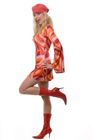 Vollständiger Körper eines attraktiven jungen Frau mit blonden Haaren trägt helle farbige sechziger oder siebziger Stil Mini-Kleid und Red Hat und rot shiney Stiefel stehend auf einem Fuß in weiß mit einem glücklichen Ausdruck begeistert  Standard-Bild